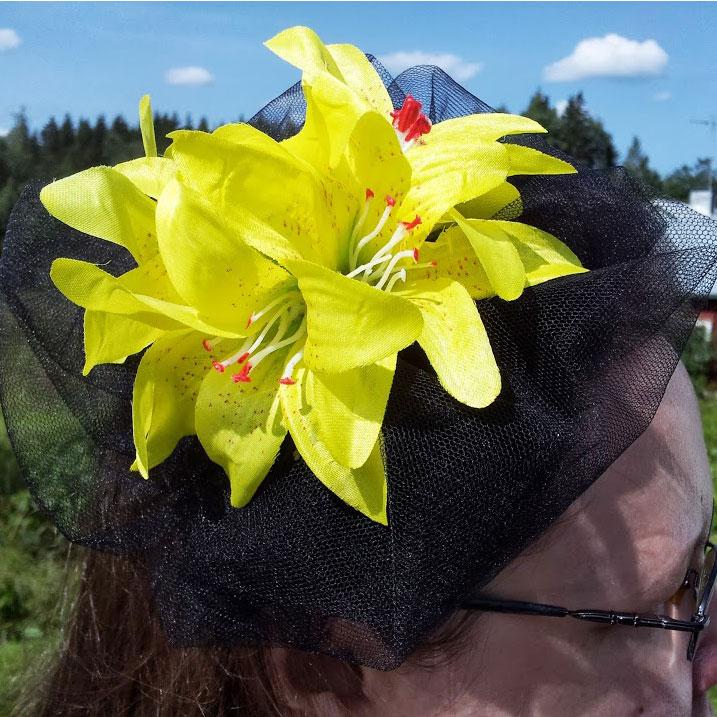 Keltaisia kukkia ja mustaa tylliä siskon pääkoristeessa.